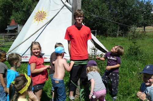 Mitarbeiter wird von Kindern an einen Marterpfahl, im Hintergrund ist ein weißes Tipi zu sehen