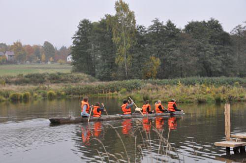 Kinder fahren mit einem Einbaum auf einem Fluss