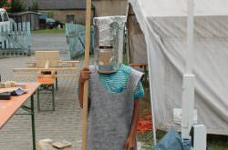 Junge in selbst angefertigter Ritterausrüstung. Lanze in der linken Hand, Helm aus Pappe und Alufolie und ein Filzgewand