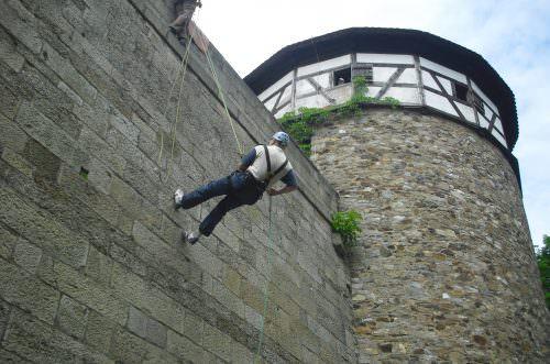 Teilnehmer seilen sich von der Burgmauer ab