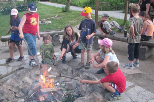 Eine Gruppe backt Stockbrot am Lagerfeuer