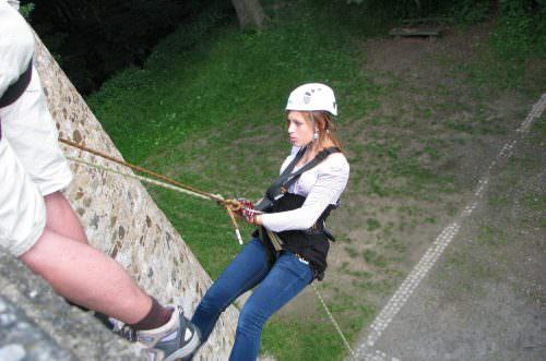 Ein Mädchen seilt sich von der Burgmauer ab