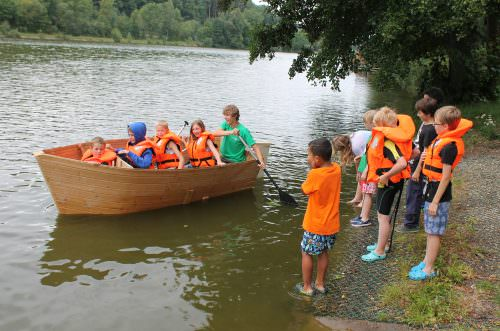 Kinder fahren mit einem selbstgebauten Boot