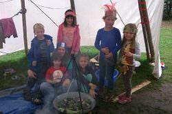 Kinder stehen als Indianer verkleidet im Tipi am Lagerfeuer