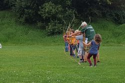 Betreuer zeigt Kinder wie man den Bogen richtig hält