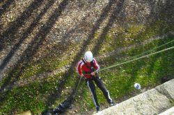 Ein Junge seilt sich von der Burgmauer ab