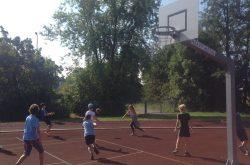 Kinder spielen gemeinsam Basketball