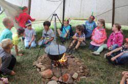 Kinder sitzen als Indianer verkleidet im Tipi am Lagerfeuer